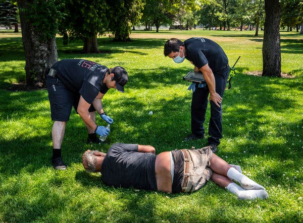 With temperatures well over 100 degrees, two firefighters — Sean Condon, left, and Lt. Gabe Mills — checked on the welfare of a man in Spokane, Wash., in late June.