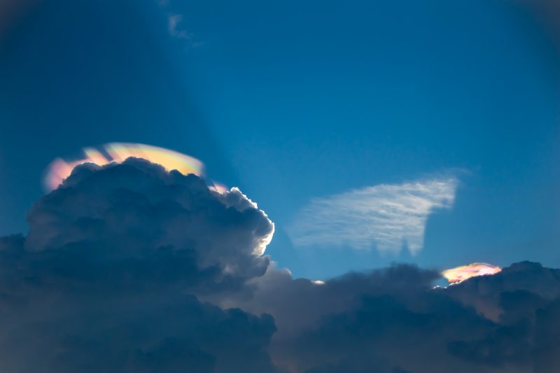 2 clouds with rainbow colors on a blue sky.