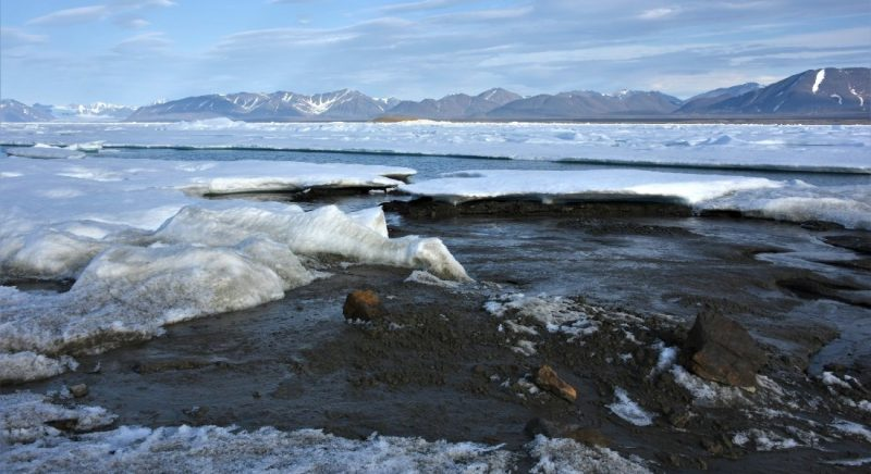 Earth's northernmost island: Piles of rock and dirt surrounded by ice and water, distant mountains.