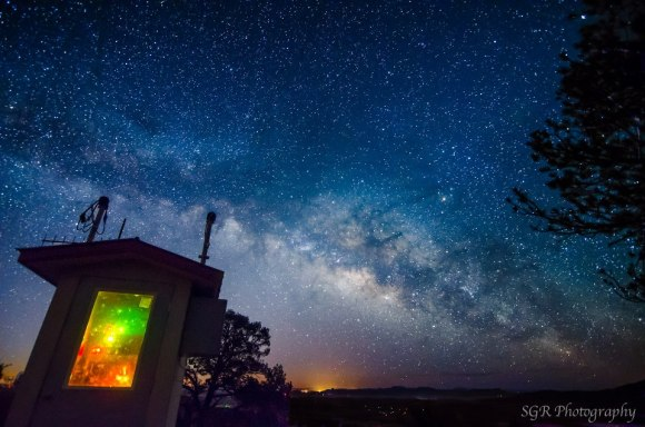 How many stars can you see: Dark night filled with stars and Milky Way, with glow on the distant horizon.