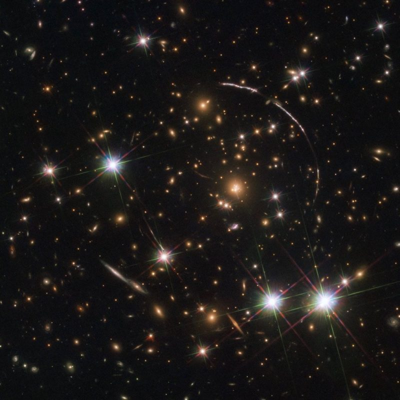 Black background dotted with spots of light, stars and galaxies, with large arcs of light.