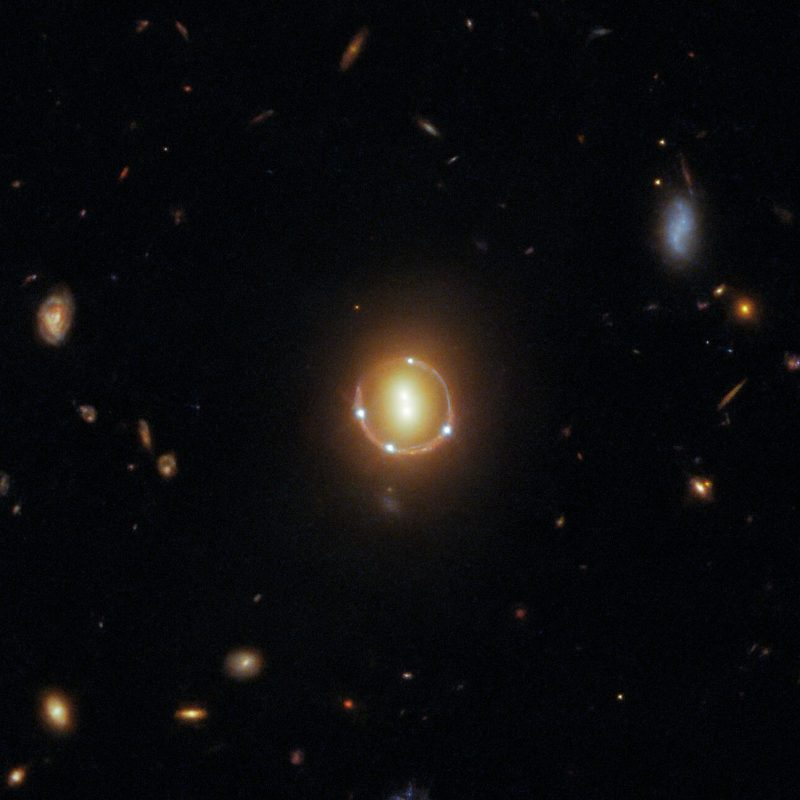 What is gravitational lensing? Two center lights inside a ring of light with four dots on ring.
