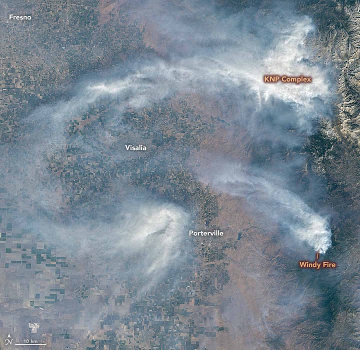 Orbital view of smoke in white clumps and swirls with towns and fires labeled.