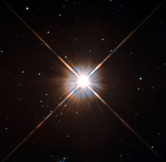 Proxima Centauri: Brilliant star with four rays with a few smaller stars scattered around.
