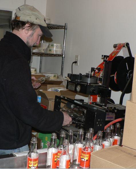 Dennis Proctor of Mother's Mountain in Falmouth labels jars for the company's popular Fire Eater hot pepper sauce.