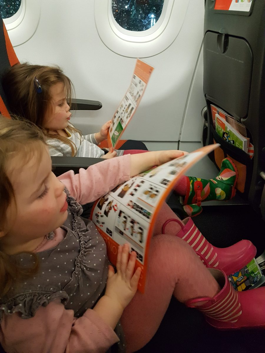 Children reading safety guidelines in airplane