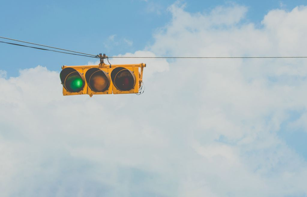 old traffic light signaling green while hanging across a blue and cloudy sky
