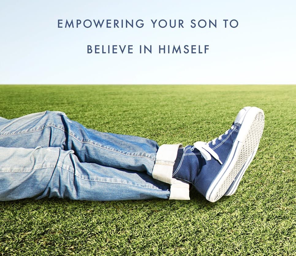 Boy wearing rolled up blue-jeans and navy converse sneakers resting in grass field