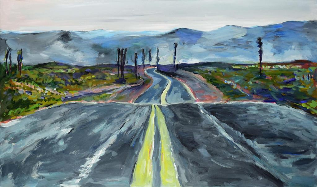 Dark windy road heading towards mountainous background