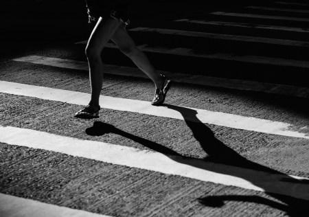 grayscale young girl running across a crosswalk