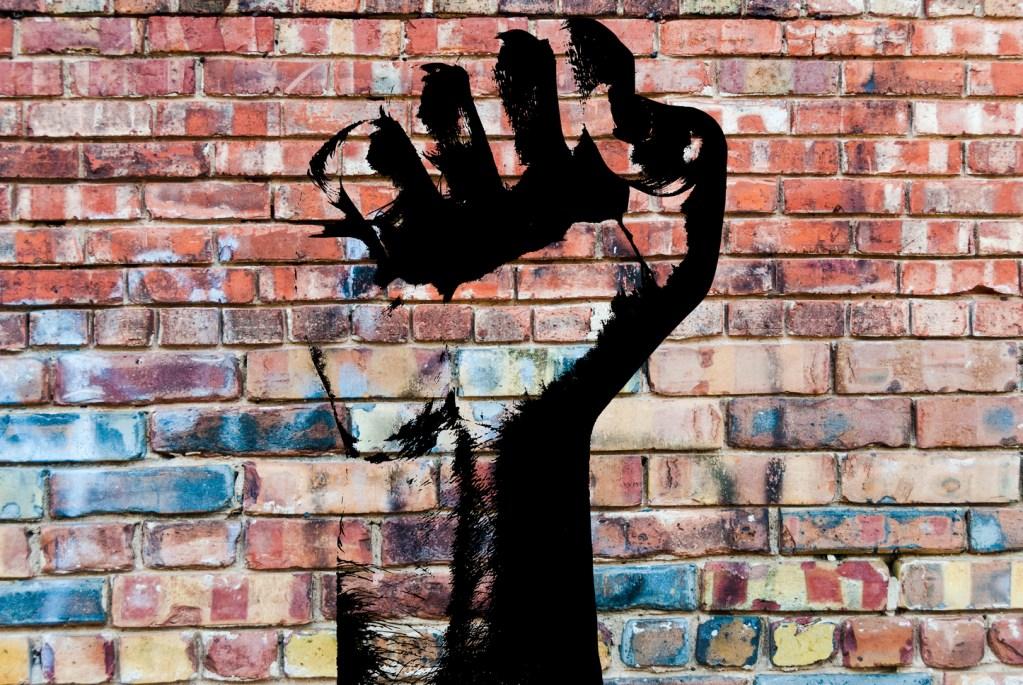 Graffiti fist on brick wall