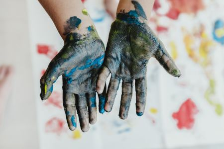Close up of hands covered with blue, yellow and gray paint