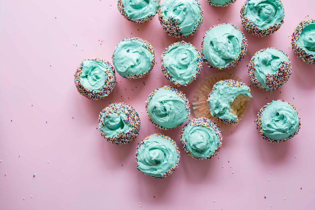 Picture from above of mint-colored iced cupcakes with rainbow sprinkles sitting on a pink background