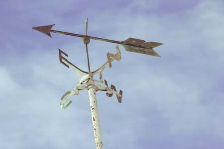 Close up of a white weathered weather vane with an arrow on top with blue sky and clouds in the background