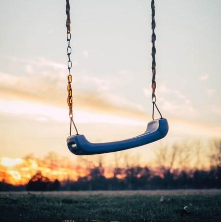 Empty blue playground seat swing and metal chain with pretty sunset in the background