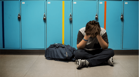 Teen boy with backpack sitting with hands in head in front of blue school lockers
