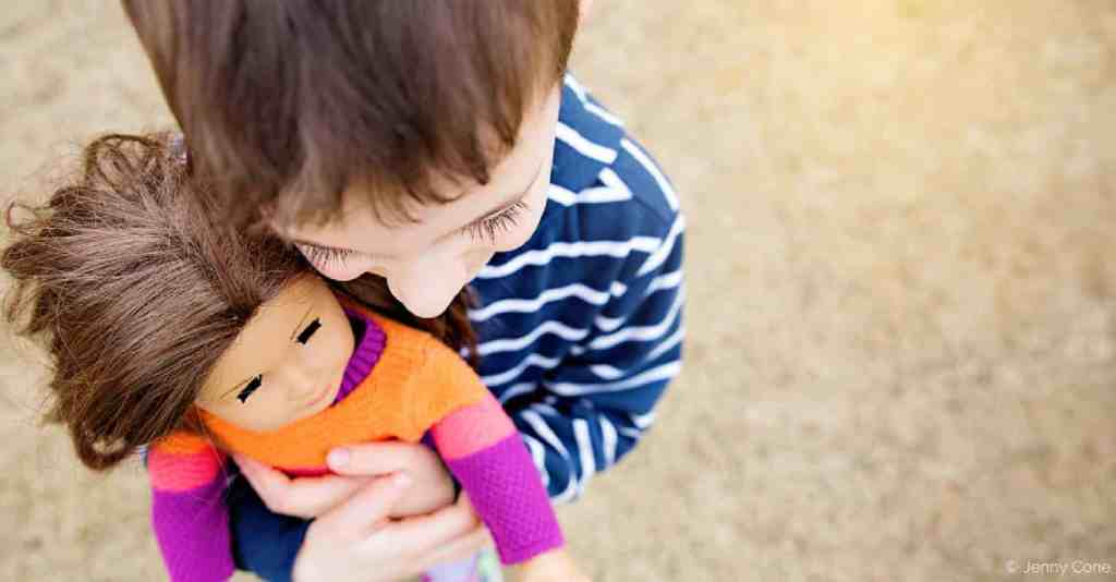Little boy wearing stripped shirt hugging doll wearing colorful sweater