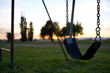 photo of an empty swing at sunset