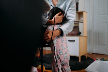 parent sitting down hugging small child in sleep suit standing up