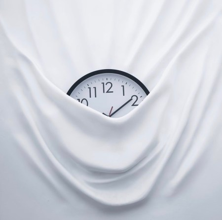 clock tucked into a white sheet