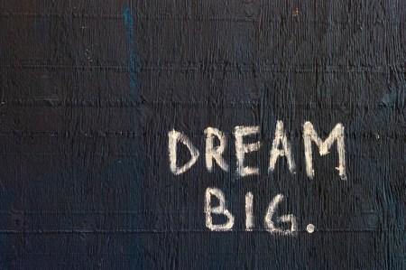 """Words """"Dream Big"""" against a black wall"""