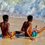 two black boys sitting in the surf