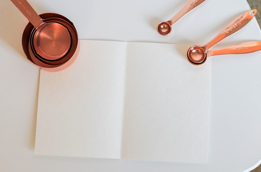 blank pages on a table held down by copper kitchen utensils
