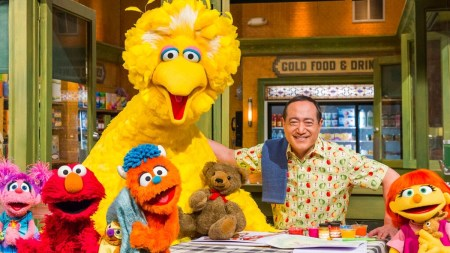 sesame street cast arms around each other at table