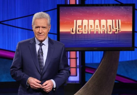 alex trebek in front of jeopardy screen