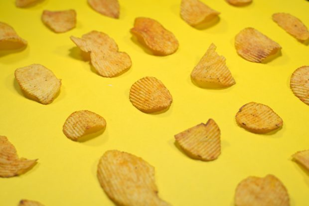 Crispy Potato Chips in Row on Yellow Background