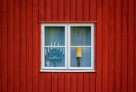 window against red pained house with Hanukkiah and light in window