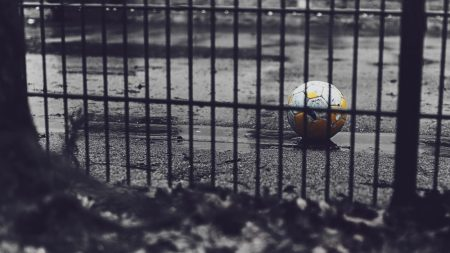 black and white of soccer ball behind fence