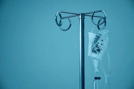 IV drip pole against blue background
