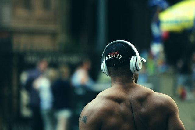 Motivation zum Sport: Ein muskulöser Mann mit Kopfhörern und Basecap