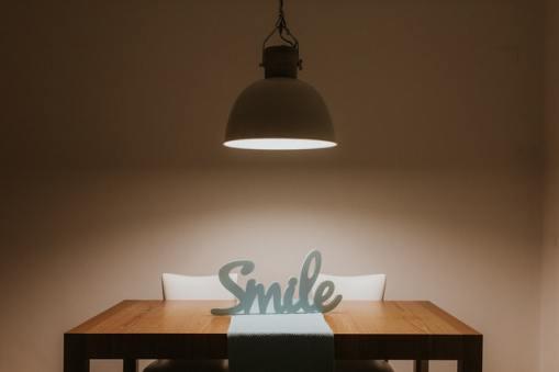 Positives Denken lernen - Smile als Wort auf einem beleuchteten Tisch