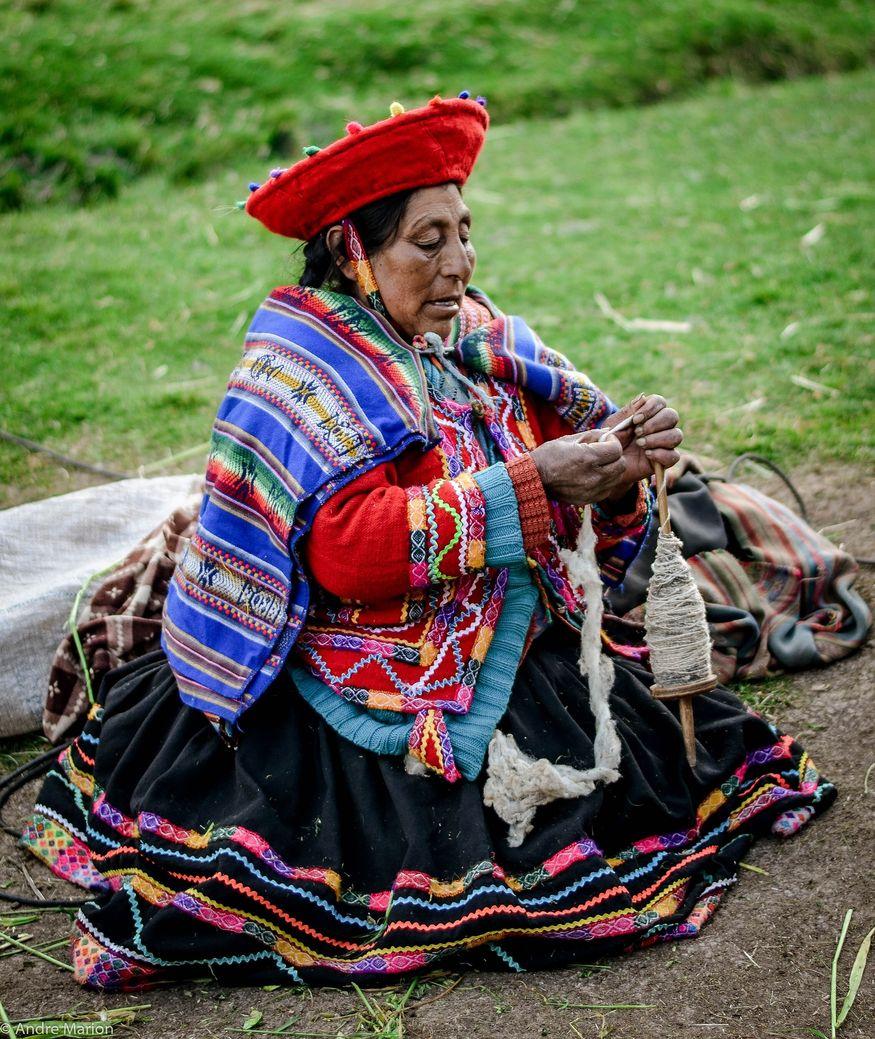 Перуанка в традиционной одежде прядет из шерсти ламы