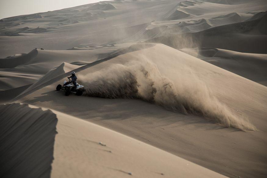 Квадроцикл взметает песок в пустыне