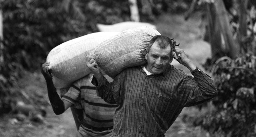Мужчина несет тяжелый мешок