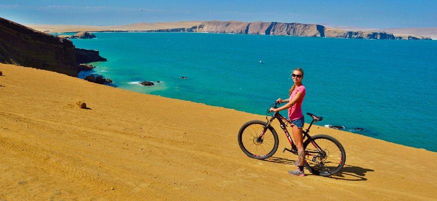 Девушка на велосипеде на краю обрыва у Тихого океана в парке Паракас