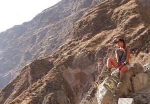 Девушка сидит на камнях в горах