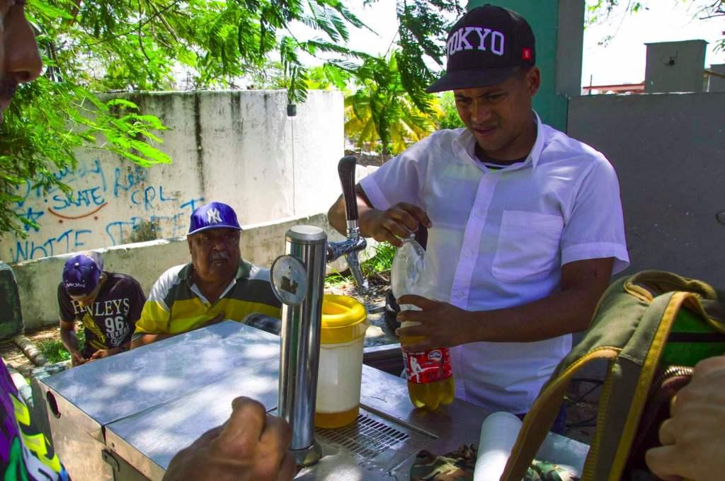 Мужчика наливает пиво в пластиковую бутылку