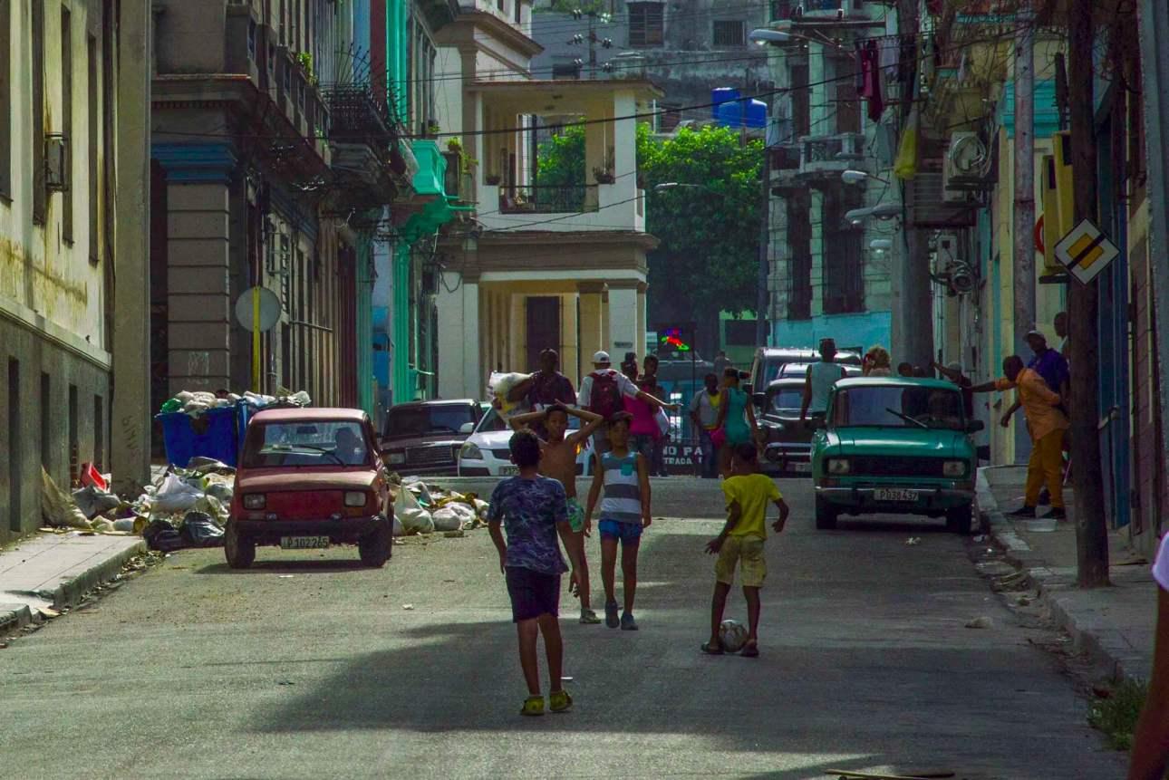 Мальчики играют в футбол в переулке