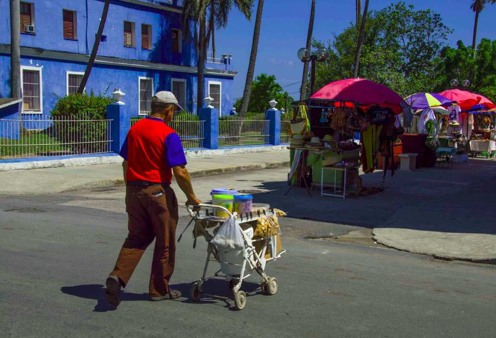 Мужчина везет по улице телегу с напитками