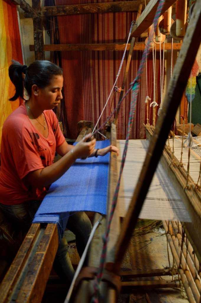 Женщина работает за ткацким станком