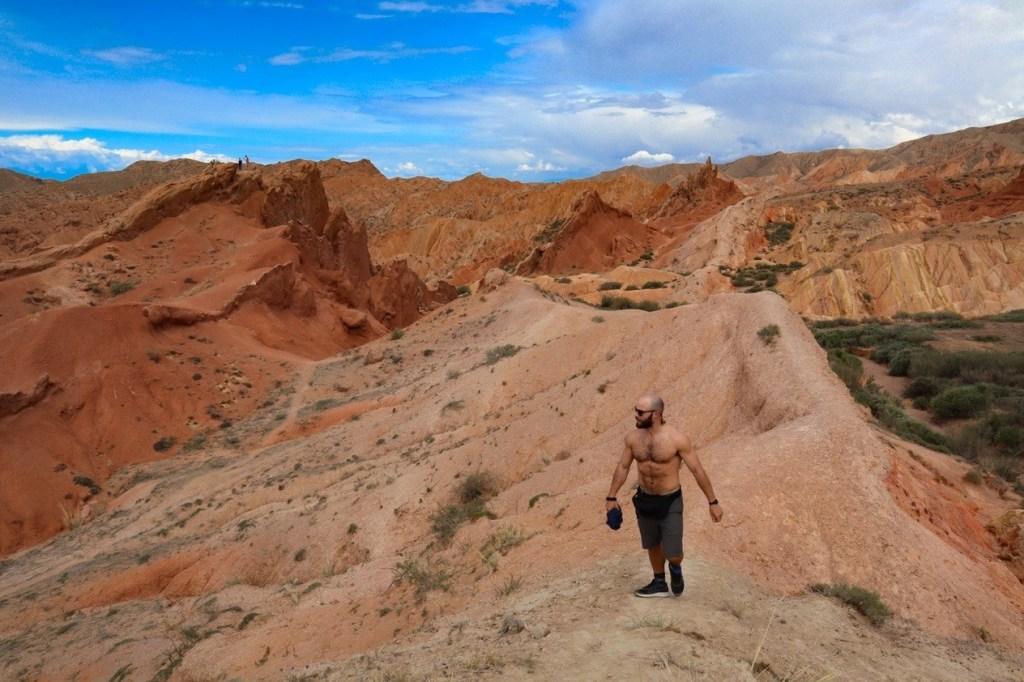 мужчина идет по гребню холма