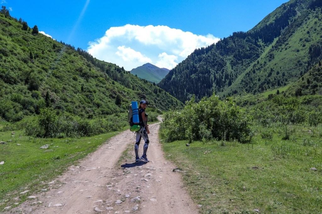 Дорога в ущелье и турист с рюкзаком