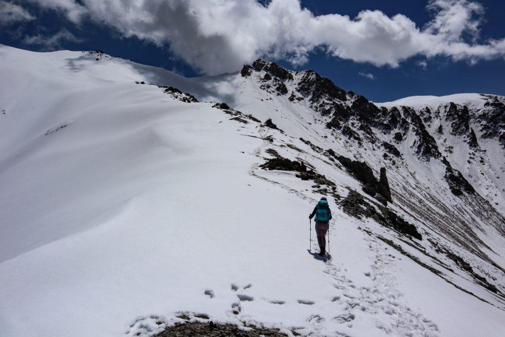 девушка идет по снегу в гору