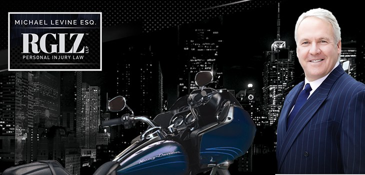 Mike Levine wearing a suit in front of a blue motorcycle in NYC at night