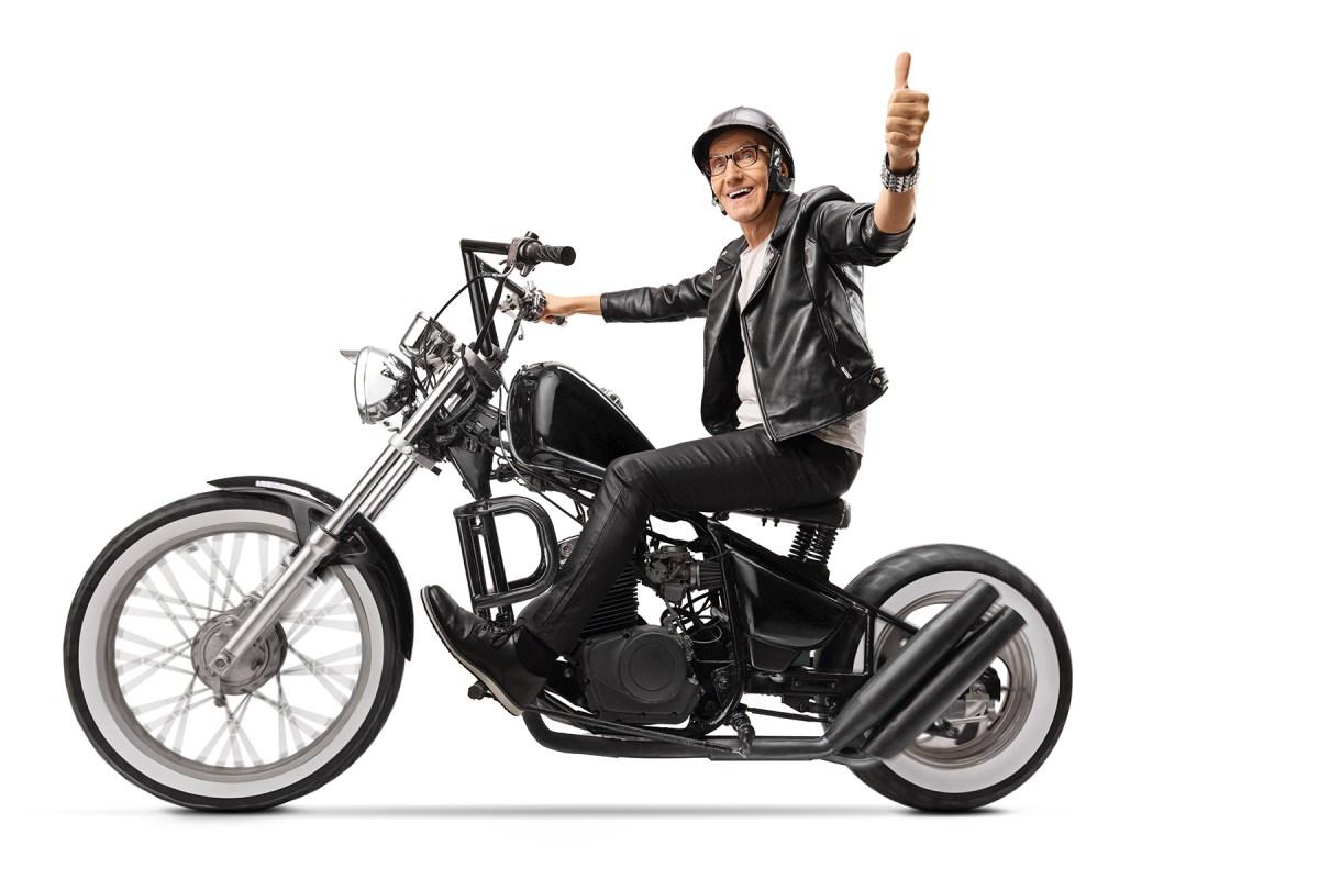 Mature biker in leather clothes riding a chopper