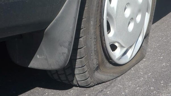 a vehicle beinmg driven with under-inflated tire that needs refilling